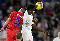 ORLANDO, FL - NOVEMBER 15: Alphonso Davies #12 of Canada heads a ball past USA's Alfredo Morales #15 during a game between Canada and USMNT at Exploria Stadium on November 15, 2019 in Orlando, Florida.