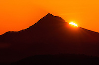 The silhouette of Mt. Hood as the sun rises from behind. Oregon.