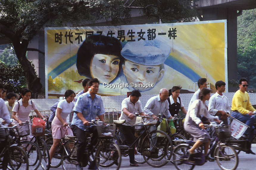 """Comuters pass a Government Propaganda poster that says """"boys and girls are equal in society"""". An average gender inbalance of 118 males to 100 females caused by the Chinese Governments One Child Policy and the  preference for boys means that there is a shortage of women in China."""