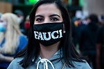A person wears a face mask that displays Dr. Anthony Fauci's name in Times Square as people gather in celebration after former Vice President Joe Biden was declared the winner of the 2020 presidential election between U.S. President Donald Trump and Biden on November 7, 2020 in New York City.  Photograph by Michael Nagle