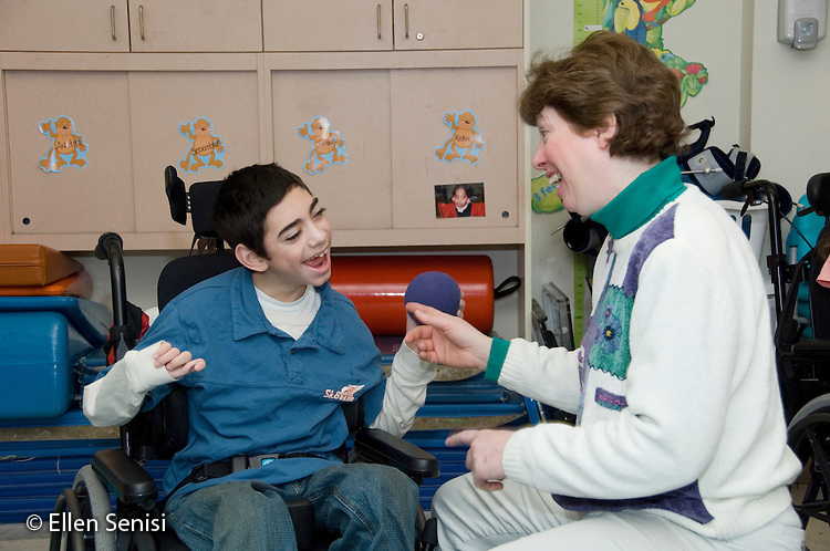 MR / Albany, NY.Langan School at Center for Disability Services .Ungraded private school which serves individuals with multiple disabilities.Physical therapist works with child in wheelchair using a small  ball. Boy: 11, cerebral palsy, expressive and receptive language delays.MR: Pie3, Bro12.© Ellen B. Senisi
