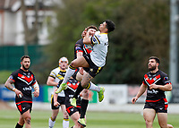 28th March 2021; Rosslyn Park, London, England; Betfred Challenge Cup, Rugby League, London Broncos versus York City Knights; Kieran Dixon of York City Knights leaps to catch the ball while being challenged by Ed Chamberlain of London Broncos