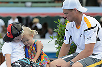 MELBOURNE, AUSTRALIA - JANUARY 12: LLEYTON HEWITT (AUS) waits to collect his trophy with his children Cruz and Ava after winning the 2013 AAMI Classic event against JUAN MARTIN DEL POTRO (ARG) 6-1 6-4 at the Kooyong Lawn Tennis Club in Melbourne, Australia. (Photo Sydney Low)