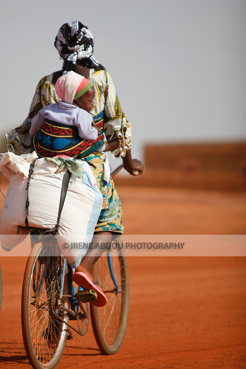 In the town of Djibo in northern Burkina Faso, a woman carries her young child strapped to her back as she rides through town on a bicycle.