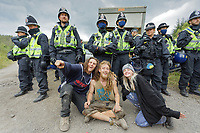 Pictured: A group of young people sit infront of a line of police officers who surrounded a van used to transport sound equipment which was confiscated. Monday 31 August 2020<br /> Re: Around 70 South Wales Police officers executed a dispersal order at the site of an illegal rave party, where they confiscated sound gear used by the organisers in woods near the village of Banwen, in south Wales, UK.