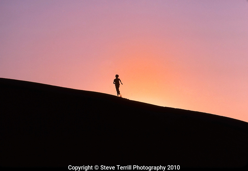My son playing on sand dune at sunset near Florence, Oregon