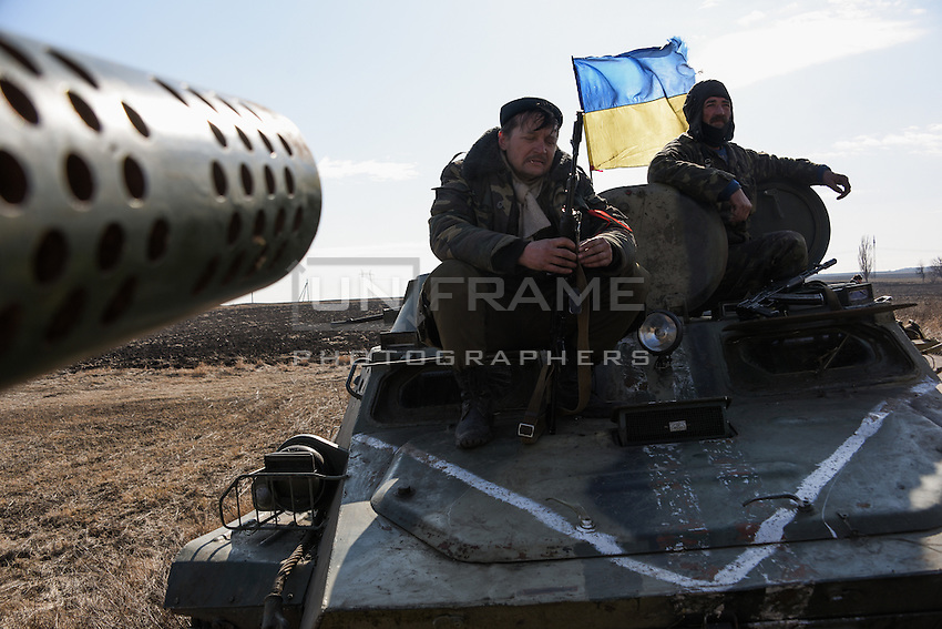 Ukrainian soldiers sit on APC preparing for departure of the convoy during the withdrawal of heavy weapons. Near Artemovsk, Eastern Ukraine. Friday, 27 February 2015.