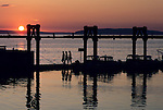 Three woman silhouetted at sunset walking on boat pier Everett Washiongton State USA