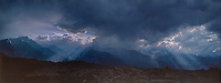 902000034 panoramic view of a clearing summer thunderstorm over the eastern sierras with god rays lighting the alabama hills in the foreground in kern county central california