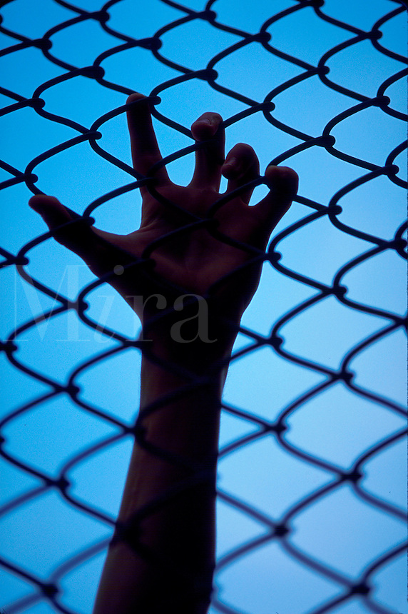 Hand holding on to a chain linked fence