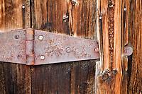 Wood siding and door hinge of historic old house. Nevada City, Montana