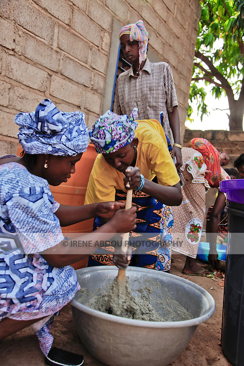 In Burkina Faso, West Africa, Muslim families celebrate the birth of a child on the 7th day after birth.  Women throughout Ouagadougou - friends and family - congregate at the mother's house on the morning of the baptism to help cook for guests.  Here, women stir pounded millet with water to make a traditional millet drink.