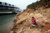 CHINA. Hubei Province. A woman colecting firewood on the banks of the Yangtze near the 3 Gorges.  The flooding of the three Gorges, by damming the Yangtze near the town of YiChang, has remained a controversial subject due to the negative environmental consequences and the displacement of millions of people in the flood plain. The Yangtze River however is reported to be at its lowest level in 150 years as a result of a country-wide drought. It is China's longest river and the third longest in the world. Originating in Tibet, the river flows for 3,964 miles (6,380km) through central China into the East China Sea at Shanghai.  2008.