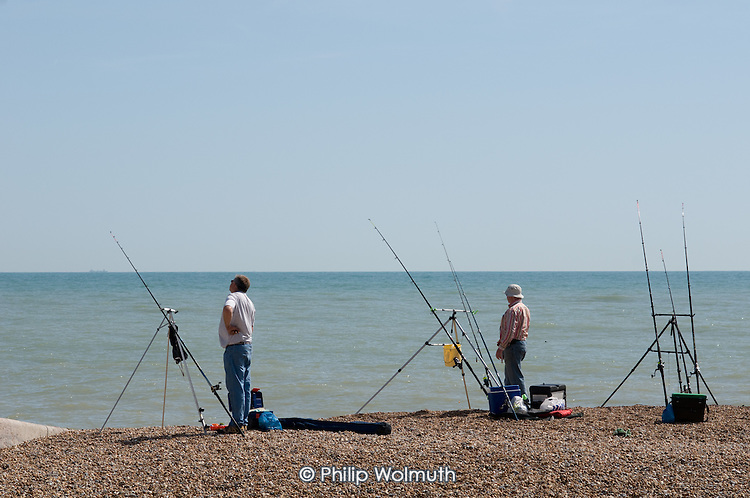 Two men with fishing rods on the shingle beach at Hastings, East Sussex.