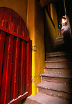 red door and man descending stairs at Cyunsi monastery in Chongqing, China, Asia