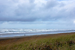 """A walker takes a beach hike on the Long Beach Penninsula, Washington State.  This access to """"The World's Longest Beach"""" is under the arch in the city of Long Beach.  The penninsula separates Willapa Bay from the Pacific Ocean. Olympic Peninsula"""