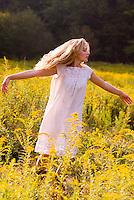 Blonde woman wearing white dress in field of goldenrod<br />