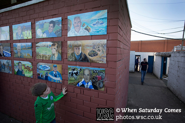 A home fan entering the ground at a turnstile by the Memorial Wall at Palmerston Park, Dumfries before Queen of the South hosted Dundee United in a Scottish Championship fixture. The home has played at the same ground since its formation in 1919. Queens won the match 3-0 watched by a crowd of 1,531 spectators.