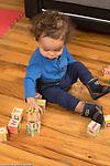 18 month old toddler boy playing with blocks making stack of 3 blocks