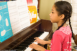 10 year old girl at home playing musical instrument piano