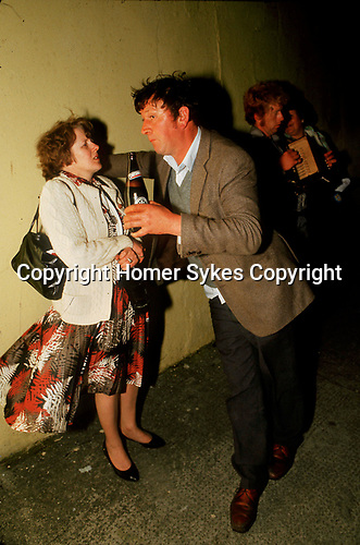 Drunk man dominating woman, drinking a bottle of beer. The annual Lisdoonvarna matchmaking festival County Clare. West coast Ireland 1990s <br /> t's 3.30 AM outside The Ritz Hotel and everyone is having their own party.