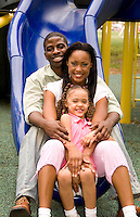 African American couple with daughter on slide in park.