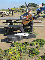 Visitor Doug Vanderberg, plays his guitar perched on a picnic table at Bean Hollow State Beach,
