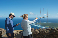 NOAA researcher Dr. Charles Littnan holds receiver while Duke University PhD candidate Kenady Wilson turns a VHF antenna to locate a Hawaiian monk seal, Neomonachus schauinslandi, carrying a Crittercam and tracking instrumentation package, Kalaupapa Lookout, Molokai, Hawaii, USA, Ho Ike a Maka Project