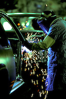 Welder with protective hood works on a automobile production line