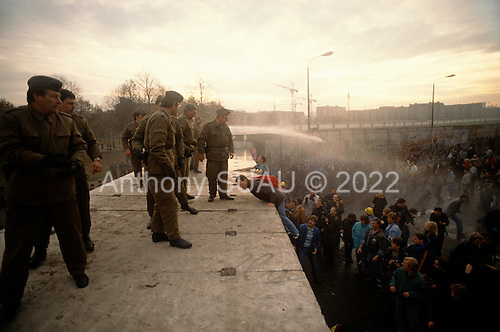 Berlin, Germany<br /> November 11, 1989<br /> <br /> East German police spray water on people climbing at the Berlin Wall near Brandenburg  Gate. The East German government lifted travel and emigration restrictions to the West on November 9, 1989.