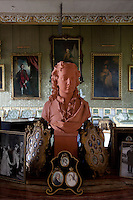 A terracotta bust of the young Earl of Coventry stands amongst framed miniatures and family photographs in the ballroom