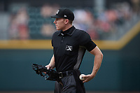 Home plate umpire Dylan Bradley works the game between the Greensboro Grasshoppers and the Winston-Salem Dash at Truist Stadium on June 19, 2021 in Winston-Salem, North Carolina. (Brian Westerholt/Four Seam Images)