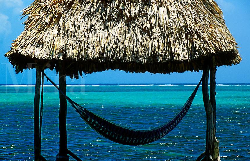 Cabana with hammock overlooking aqua tropical waters, Ambergris Caye, Belize<br />