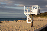 On an early October day the lifeguard's tower  is un-manned. A dog walks along the empty beach.