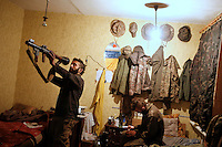 """UKRAINE, 02.2016, Novohrodivka, Oblast Donetsk. Ukrainian-Russian conflict concerning Eastern Ukraine / Foreign volunteers (""""Task Force Pluto"""") fighting with the far-right militia Pravyi Sektor against the Russian-backed separatists: Ben and Alex (Austria) cleaning guns and an RPG-7 launcher in their sleeping room at the base after returning from the frontline. © Timo Vogt/EST&OST"""