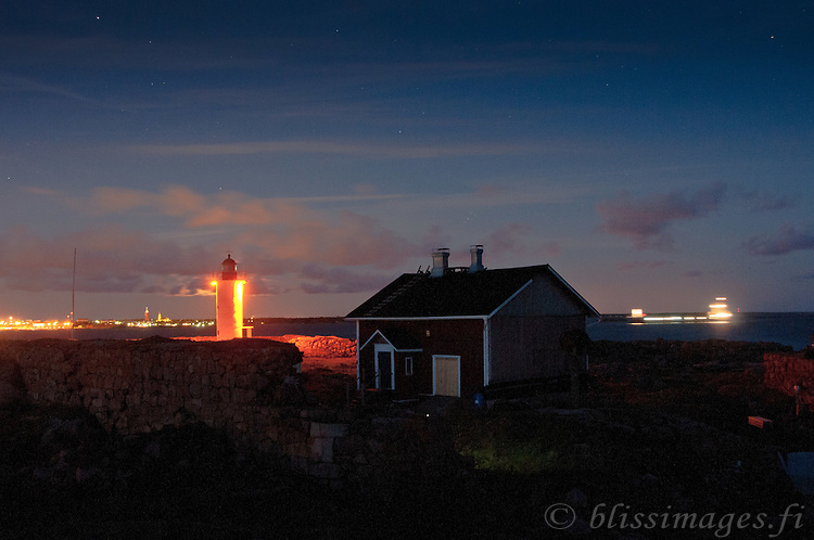 Ship passing Gustavsvärn Lighthouse and entering Hanko harbour at night -Finland