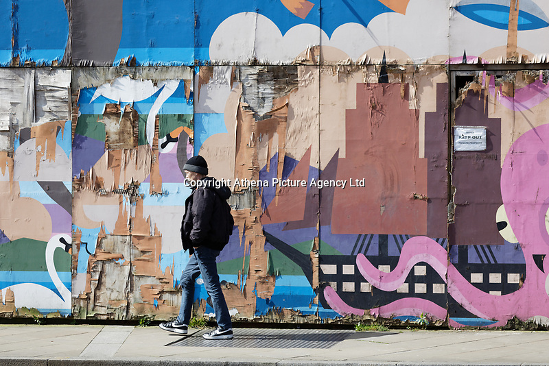Pictured: A man walks past a graffitied property in the High Street, Swansea, Wales, UK.<br /> Re: The owner of The White Swan pub is closing down after anti-social behaviour, violence, drugs and prostitution in the High Street, Swansea, Wales, UK.