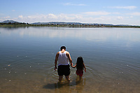A Chinese man and child walk into the Yalu River which separates China and North Korea.
