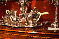 Interior of an antique shop in the San Telmo district around Plaza Dorrego Square, silver tea or coffee set with samovar, cream pot coffee pot handles in ivory standing on a chest of drawers with wood inlays. Calle Defensa Defence street Buenos Aires Argentina, South America