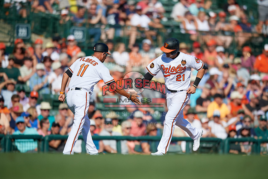 Baltimore Orioles left fielder Austin Hays (21) is congratulated by third base coach Jose David Flores (11) as he rounds third base after hitting a home run in the bottom of the third inning during a Grapefruit League Spring Training game against the Detroit Tigers on March 3, 2019 at Ed Smith Stadium in Sarasota, Florida.  Baltimore defeated Detroit 7-5.  (Mike Janes/Four Seam Images)