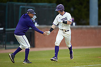 Justice Bigbie (18) of the Western Carolina Catamounts slaps hands with third base coach Bobby Moranda after hitting a home run against the St. John's Red Storm at Childress Field on March 13, 2021 in Cullowhee, North Carolina. (Brian Westerholt/Four Seam Images)