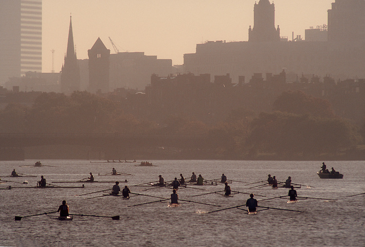 Rowers in single racing shells await their start of the Head of the Charles Regatta past Nob Hill and Boston's highrise buildings at dawn, Massachusetts, New England, USA.