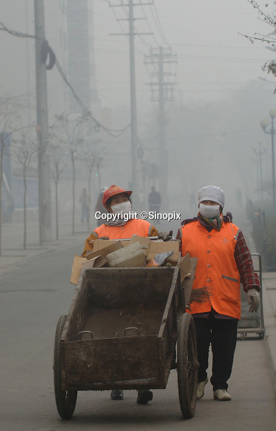 Street cleaners of Lanzhou wear protective masks in Gansu Province, China. The city is the most polluted in China..22 Nov 2005