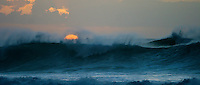 The sun sets behind a wave and clouds at Pipeline on Oahu's North Shore.