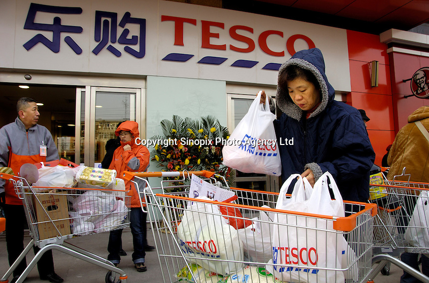Shoppers waiting outside the British retail giant Tesco in Beijing, China. It is the first Tesco own-brand supermaket opened in China..27 Jan 2007