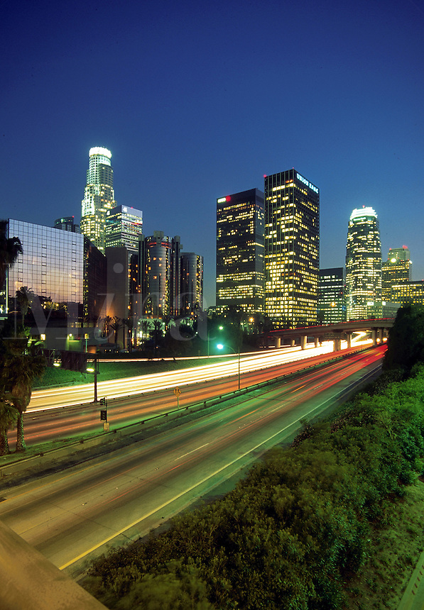 The city skyline of Los Angeles at dusk with the blurred lights of traffic in motion in the foreground. California.