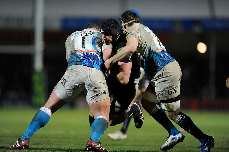 Ben White of Exeter Chiefs (centre) is tackled by David Flatman (left) and Guy Mercer of Bath Rugby during the LV= Cup match between Exeter Chiefs and Bath Rugby at Sandy Park Stadium on Sunday 5th February 2012 (Photo by Rob Munro)