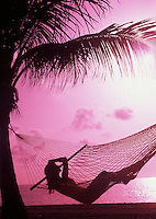 Silhouette, young woman in hammock at the beach at sunset