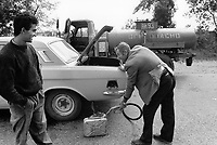 """Russia. Krasnodar Krai Region. Krasnodar. A fuel tanker truck is parked on the asphalt road and sells gasoline. On its sides, the words written in cyrillic language """" Flammable and 93-octane fuel"""". Once the Lada car's tank filled with petrol, the truck driver fills also a jerrycan. The car owner talks and jokes with the gas station attendant. LADA is a brand of cars manufactured by AvtoVAZ (originally VAZ), a Russian company owned by the French Groupe Renault. Krasnodar (also known as Kuban) is the largest city and the administrative centre of Krasnodar Krai in Southern Russia. 25.09.1993 © 1993 Didier Ruef"""