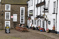 UK, England, Yorkshire, Reeth.  Two Couples Talking outside the Black Bull Hotel.